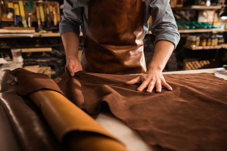 Close up of a cobbler working with leather textile at his workshop