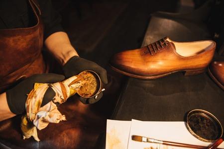 Bijgesneden afbeelding van jonge geconcentreerde man schoenmaker bij schoenen workshop.