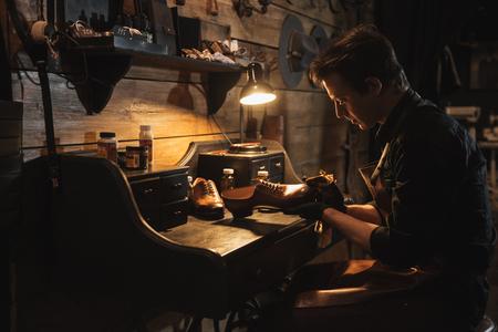 Afbeelding van jonge geconcentreerde man schoenmaker bij schoenen workshop.