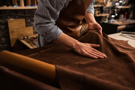 Close up of a male shoemaker working with leather textile at his workshop