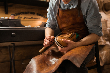 Cropped picture of young shoemaker in workshop making shoes. Stock Photo