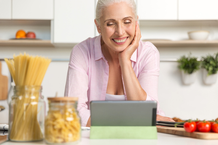 Picture of pretty mature woman standing at the kitchen cooking while using tablet computer. Looking aside.