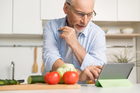Image of concentrated mature man wearing glasses standing at the kitchen cooking salad using tablet computer. Looking aside.