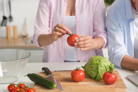 Bebouwd beeld van rijpe houdende van paarfamilie die zich bij keuken het koken bevinden.