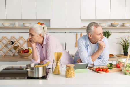 Image of serious mature loving couple family standing near each other looking at different sides at the kitchen.