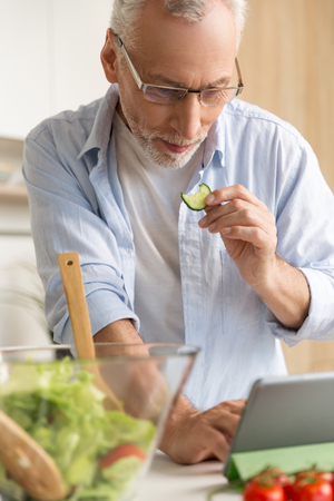 Image of handsome concentrated mature man wearing glasses standing at the kitchen cooking salad using tablet computer. Looking aside.