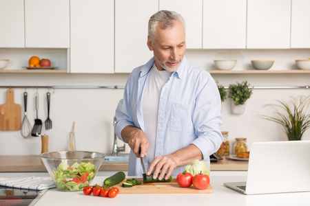 Picture of mature handsome man standing at the kitchen using laptop computer and cooking salad. Looking aside.