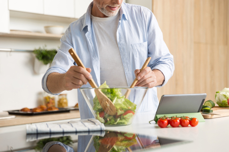 Cropped image of mature man standing at the kitchen cooking salad using tablet computer.