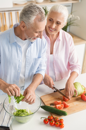 Image of happy mature loving couple family standing at the kitchen and cooking salad. Looking aside. Stock Photo