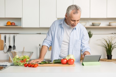 Picture of handsome mature man standing at the kitchen cooking salad. Using tablet.