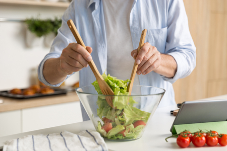 Cropped photo of mature man standing at the kitchen cooking salad using tablet computer. Zdjęcie Seryjne