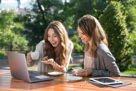Photo of smiling young two women sitting outdoors in park drinking coffee using laptop computer. Looking aside.