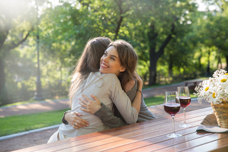 Picture of happy young two women sitting outdoors in park drinking wine. Looking aside and hug.