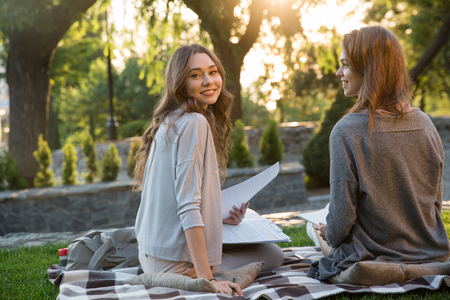 Picture of cheerful young two women sitting outdoors in park writing notes. Looking camera.