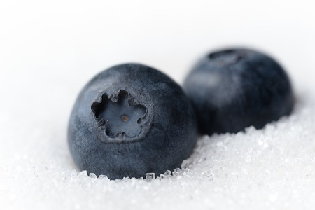 Picture of sweet blueberries isolated over white sugar background.