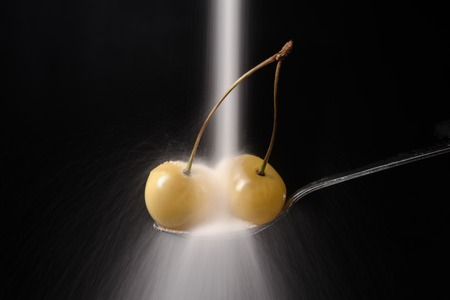 gean: Sugar pours on the spoon with sweet cherry isolated over black background.