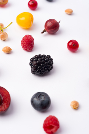 Photo of mix of berries isolated over white background table.