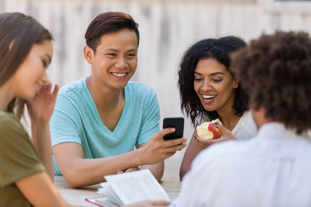 Picture of cheerful young multiethnic group of friends students talking with each other outdoors using mobile phone. Looking aside. photo