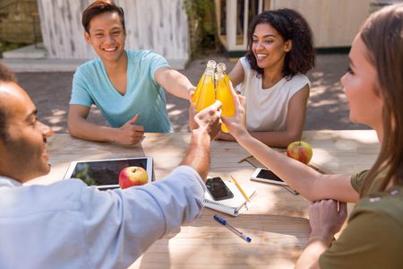 Image of happy young multiethnic friends students outdoors drinking juice and talking with each other. Looking aside. photo