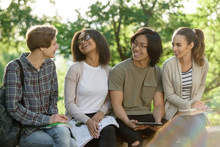 Picture of multiethnic group of young cheerful students sitting and studying outdoors. Looking aside. photo