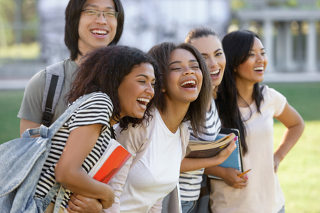Picture of multiethnic group of young happy students standing outdoors. photo