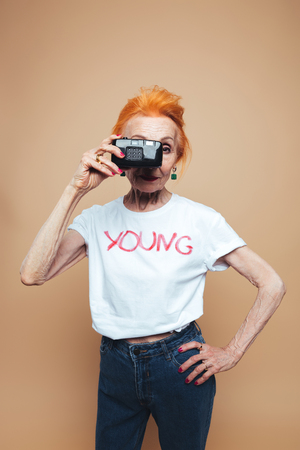 Beeld van de schitterende rijpe vrouw van de roodharigemanier status geïsoleerd bij studio en holdingscamera