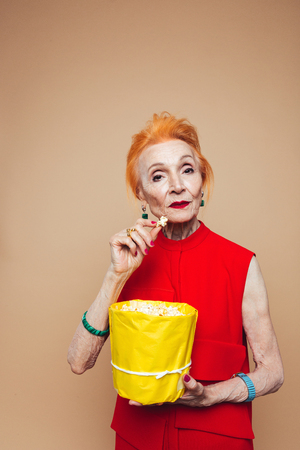 Image of amazing mature redhead fashion woman standing isolated at studio eating popcorn. Looking camera.