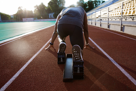 Back view of a young male athlete at starting block on running track