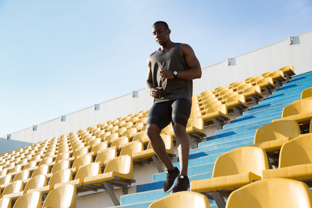 Young african man runner in sport clothes running downstairs at the stadium