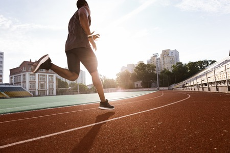 Athlete african man running on racetrack at a stadium