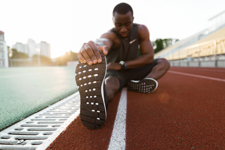 Young concentrated african male athlete stretching legs while sitting at the stadium race track