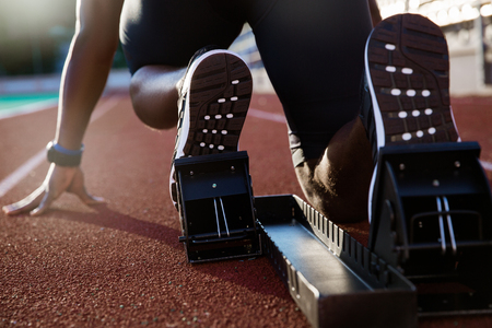 Back view of men's feet on starting block ready for a sprint start Stockfoto