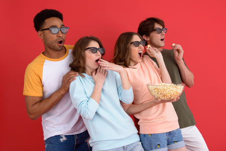 Image of young shocked group of friends standing isolated over red background. Looking aside watching film eating popcorn.