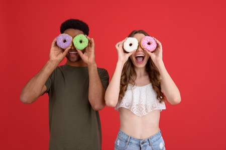 Picture of young happy two friends standing with donuts isolated over red background. Looking at camera. Фото со стока