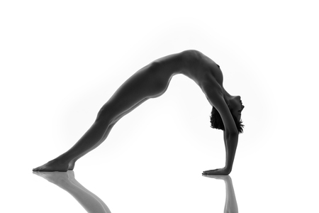 Beautiful healthy woman practicing yoga over white background. Black and white photo style