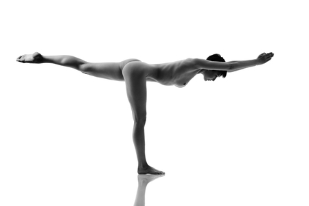 Young nude woman in yoga position over white background. Black and white photo style Stock Photo