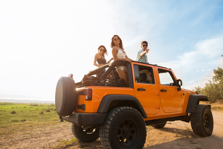 Happy cheerful friends on a road trip standing in a convertible car Stock Photo