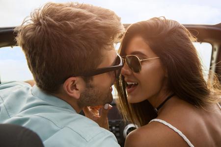 美しい若いカップルの車に坐っている間キスのクローズ アップ 写真素材
