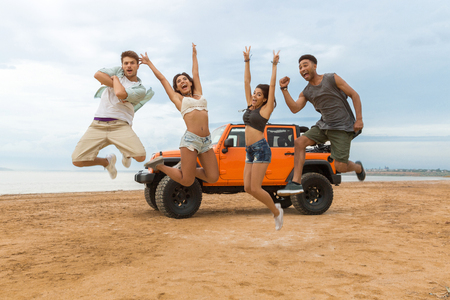 Group of happy multiethnic friends jumping in front of their car with hands raised and having fun at the beach 免版税图像