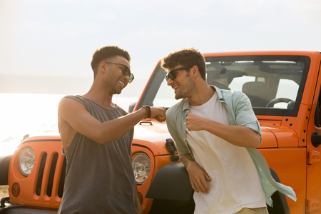 Two happy male friends having a good time together at the beach with a car on background Stock Photo