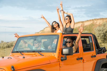 Group of happy multiethnic friends having fun by travelling together by a car