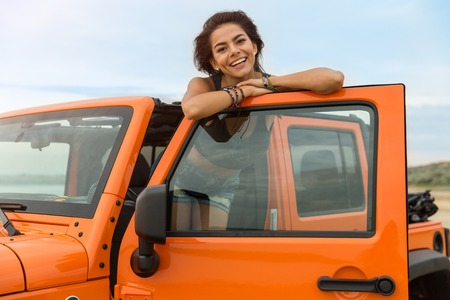Smiling attractive woman leaning on a car door and looking at camera at the beach Stock Photo