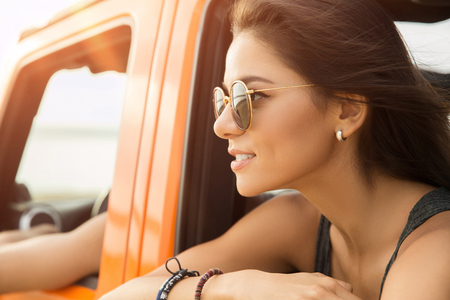 Close up of a happy smiling woman sitting and looking out of the window in a car