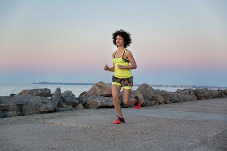 若い健康的なスポーツ、ビーチに沿ってジョギングの女性