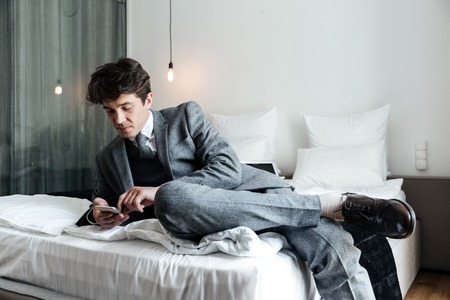 comfortable: Businessman using smartphone while lying on a bed in a hotel room during a business trip