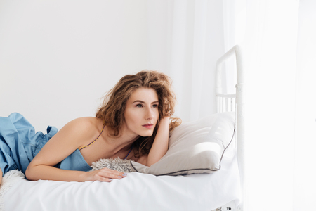 comfortable: Image of beautiful young woman lies indoors in bed. Looking aside. Stock Photo
