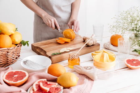 Cropped picture of young woman standing indoors near table with a lot of citruses and cut the orange. Stock Photo