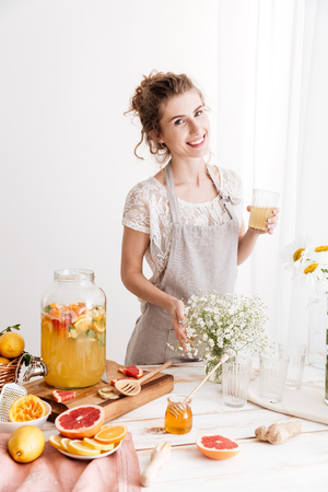 Picture of amazing happy woman standing indoors drinking citrus beverage. Looking camera.