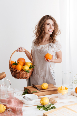 Picture of happy young woman standing indoors holding basket with a lot of oranges. Looking aside. Stock Photo