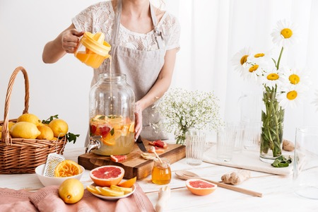 Cropped photo of amazing concentrated woman standing indoors cooking citrus beverage.